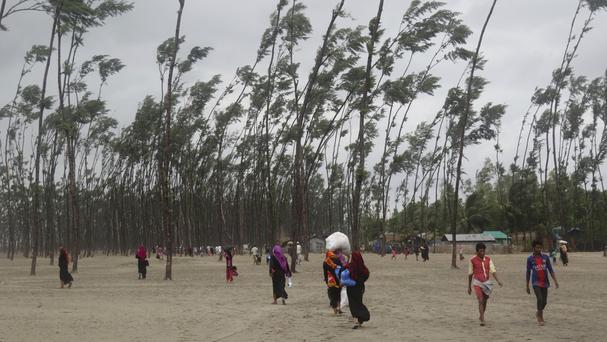 Bangladeshis carry their belongings and walk home after spending a night at a shelter in Cox's Bazar (AP)