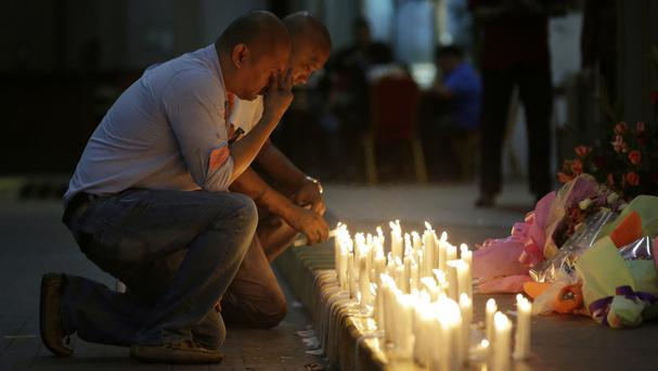 A man holds back tears as he lights candles for victims in an attack at the Resorts World Manila complex (Aaron Favila/AP/PA)