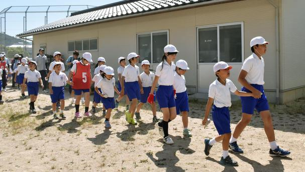 Children leave their school during the drill (Kyodo News/AP)