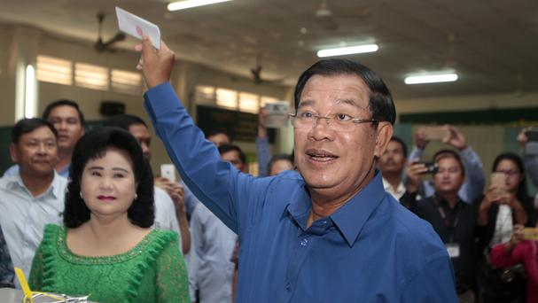 Cambodian prime minister Hun Sen shows off his ballot paper as his wife Bun Rany looks on (AP)