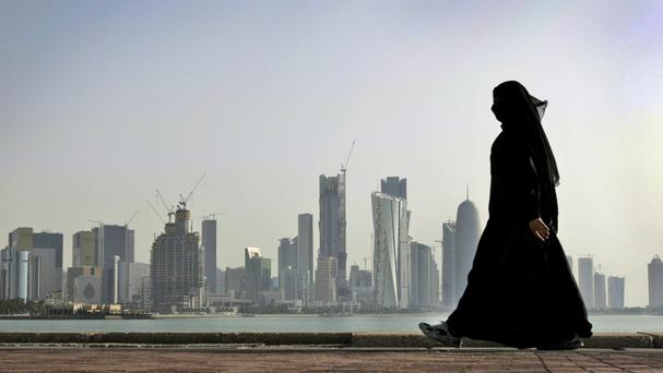 A Qatari woman walks in front of the city skyline in Doha after four Arab countries severed ties with their neighbour (Kamran Jebreili/AP)