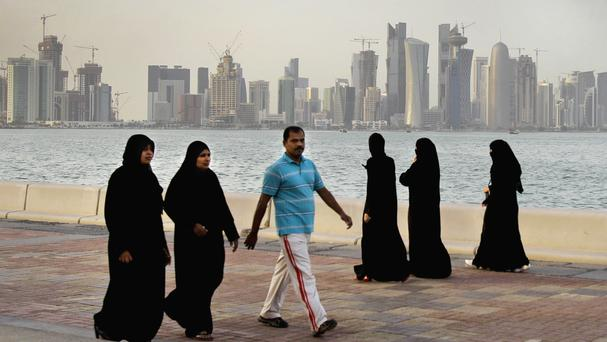 Qataris walk by the sea in front of the Doha skyline (Kamran Jebreili/AP)