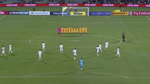 Players from the Saudi Arabian team walk on the field as Australian players line up for a minute of silence (Lagardere Sports/AP)