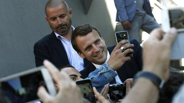 President Emmanuel Macron poses for a selfie as he arrives at his house in Le Touquet (AP/Thibault Camus)