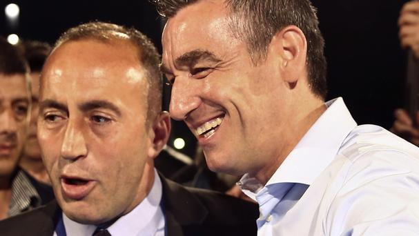 Ramush Haradinaj, left, is joined by coalition partner Kadri Veseli claiming electoral victory (AP)