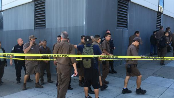 UPS workers gather outside after a reported shooting at a UPS warehouse and customer service centre in San Francisco (AP)