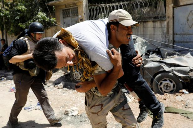 An Iraqi soldier carries a journalist wounded due to fighting between Iraqi forces and Isil militants in Mosul. Photo: Reuters