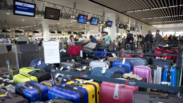 Passengers check in among left pieces of luggage at Brussels Zaventem Airport in Brussels (AP)