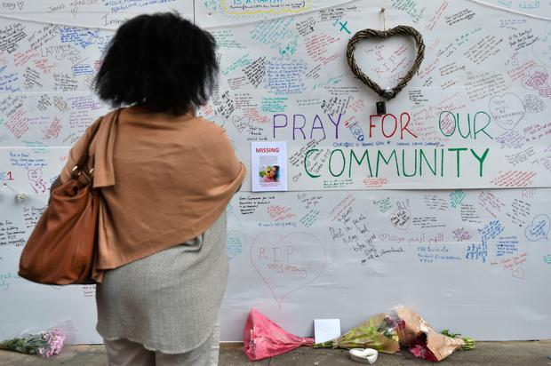A woman reads a wall of tributes close to Grenfell Tower in west London yesterday morning. Photo: PA