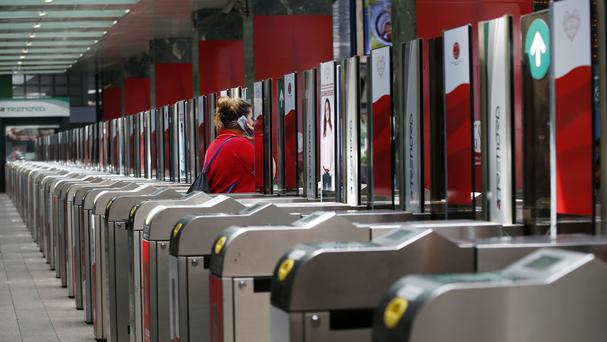 A woman enters a train station during the general transport strike in Milan (AP)