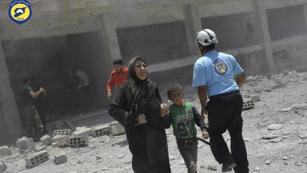 People rush out of damaged buildings after air strikes in the western part of the southern Daraa province of Syria (Syrian Civil Defence White Helmets via AP)