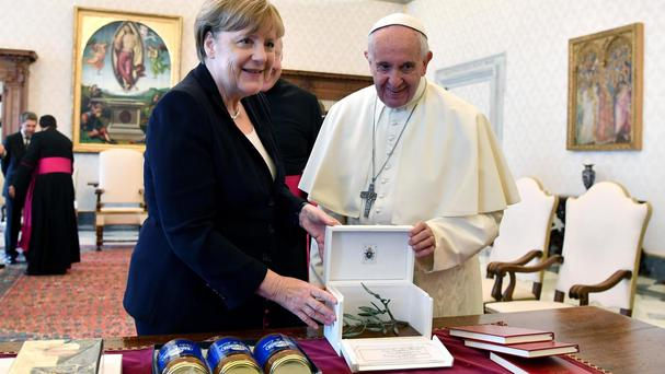 Pope Francis and German Chancellor Angela Merkel exchange gifts (Ettore Ferrari/Pool Photo via AP)