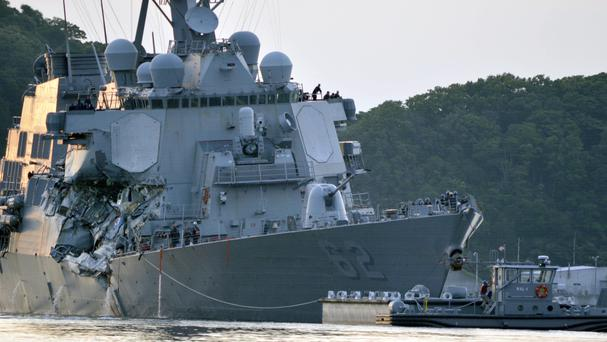 The damaged USS Fitzgerald is towed into port at the US naval base in Yokosuka (US Navy/AP)