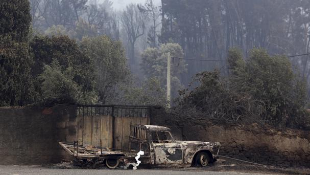 A burnt truck next to a gate in the village of Pobrais, near Pedrogao Grande, central Portugal (Armando Franca/AP)