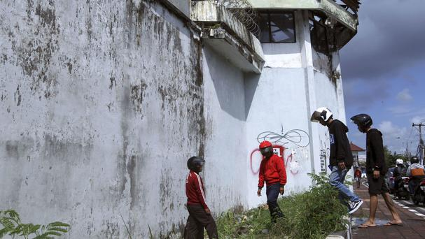 Residents look at a hole in the ground through which four foreign inmates have escaped from Kerobokan prison in Bali, Indonesia (Firdia Lisnawati/AP)