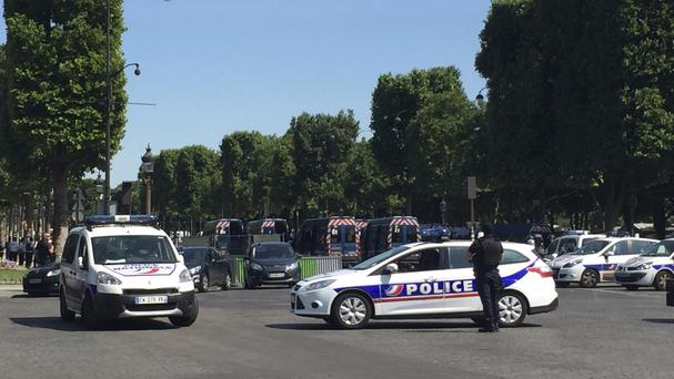 Police vehicles prevent access to the Champs Elysees avenue in Paris (Bertrand Combaldieu/AP)
