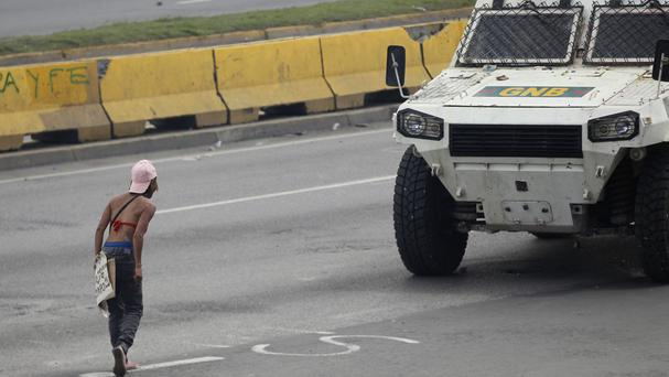 An anti-government demonstrator challenges a National Guard armoured vehicle during clashes in Caracas (AP)