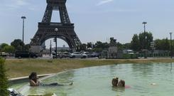 Girls swim in the fountain of the Trocadero gardens in Paris (Thibault Camus/AP)