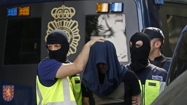 Police lead a suspect from an apartment after a search in Madrid (Francisco Seco/AP)