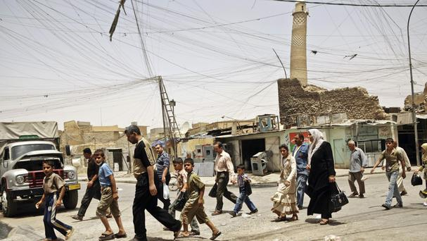 Residents walk past the crooked minaret in a busy market area in Mosul (Maya Alleruzzo/AP)