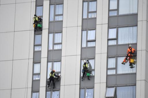 Window cleaners work on a tower block on the Chalcots Estate in Camden which has aluminium cladding which the local council has decided to remove. Photo: Reuters