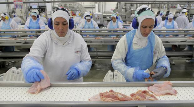 Workers prepare poultry at the meatpacking company JBS in Lapa, Brazil (AP)