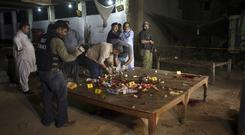 Investigators collect evidence from the site of a shooting in Karachi