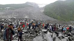 Emergency personnel and locals work at the site of the landslide in Xinmo village (Chinatopix)