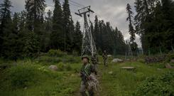 Indian army soldiers walk back after a rescue mission in Gulmarg