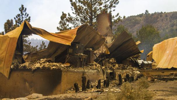 A cabin burnt to the ground by a wildfire on the west side of Panguitch Lake, Utah (Jordan Allred/The Spectrum via AP)