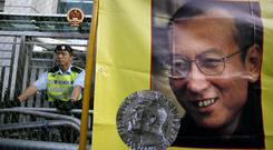 A police officer stands guard beside a picture of jailed Chinese dissident Liu Xiaobo (AP)