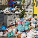 A woman walks past a pile of garbage outside a pet shop, in Piraeus, near Athens (AP)