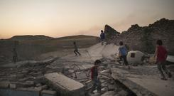 Children play on debris in a neighbourhood recently retaken by Iraqi security forces during fighting against Islamic State militants in west Mosul (AP)