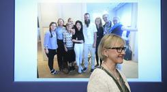 Swedish foreign minister Margot Wallstrom smiles in front of a picture of freed hostage Johan Gustafsson, centre, and his family (Marcus Ericsson /TT via AP)