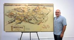 Auction house co-owner Mike Van Eaton with the first colour drawing of Disneyland (Van Eaton Galleries/AP)