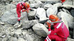 Rescuers use sensors to check for signs of life in the rubble at the site of a landslide in Xinmo village in China's Sichuan Province (Chinatopix via AP)