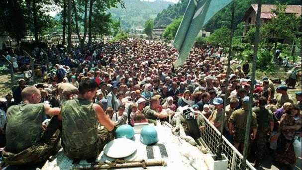 Dutch UN peacekeepers sit on top of an armoured personnel carrier as Muslim refugees from Srebrenica gather in the nearby village of Potocari (AP)