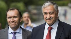 Turkish Cypriot leader Mustafa Akinci, right, smiles next to UN envoy Espen Barth Eide, in Crans-Montana (Jean-Christophe Bott/Keystone via AP)