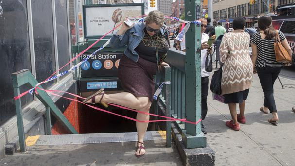 A commuter exits a closed-off station after a subway train derailment in the Harlem neighbourhood of New York (AP)