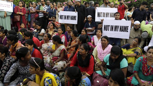 Protesters hold placards against a spate of violent attacks across India targeting the Muslim minority, in Kolkata (AP)