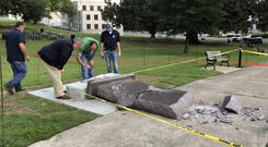 Officials inspect the damage to the new Ten Commandments monument outside the state Capitol in Little Rock. (AP)