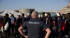 An Italian border police officer escorts migrants on their way to a relocation centre in Sicily. (AP)