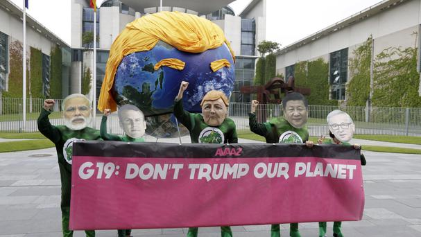 Demonstrators of the Avaaz campaign protest against the climate policy of US President Donald Trump prior to a gathering of European leaders on the upcoming G-20 summit in the chancellery in Berlin (AP)