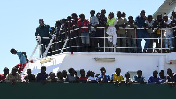 Migrants wait to disembark from the Spanish ship Rio Segura in the harbour of Salerno, Italy (Ciro Fusco/ANSA via AP)