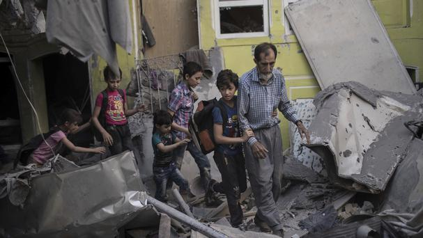 Iraqi civilians flee through a destroyed house as Iraqi special forces move toward Islamic State positions in the Old City of Mosul (AP)