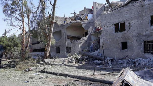 Damaged buildings at the scene of an explosion along the road to the airport in south-east Damascus, Syria (Sana/AP)