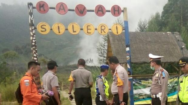 Police and a rescuer at a path leading to Sileri Crater after it erupted in Dieng, Central Java (AP)