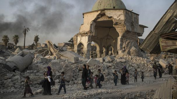 Fleeing Iraqi civilians walk past the heavily damaged al-Nuri mosque as Iraqi forces continue their advance against Islamic State militants in the Old City of Mosul (AP)