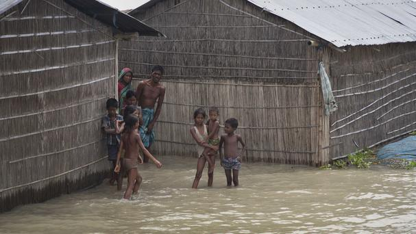 Indian villagers stand outside their houses partially submerged in flood waters in Burgaon (AP)