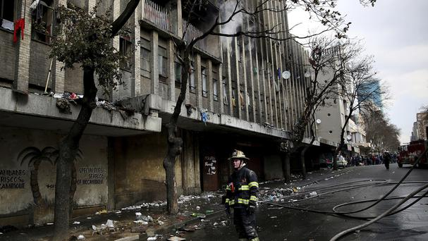 A fireman stands outside the smouldering building in central Johannesburg (AP)
